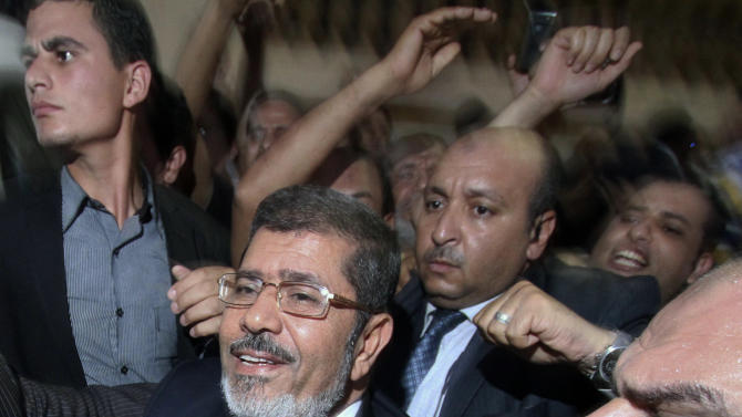 Mohammed Morsi, foreground left, and his supporters celebrate his apparent victory in the Egyptian presidential election at his campaign headquarters in Cairo, Monday, June 18, 2012. The Muslim Brotherhood declared early Monday that its candidate, Mohammed Morsi, won Egypt's presidential election, which would be the first victory of an Islamist as head of state in the stunning wave of protests demanding democracy that swept the Middle East the past year. (AP Photo/Ahmed Gomaa)