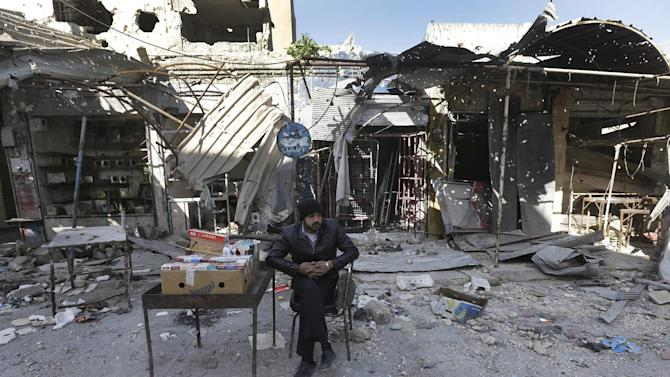 A Syrian street vendor who sells cigarette boxes, sits in front of destroyed shops which were damaged by the shelling of the Syrian forces, at Maarat al-Nuaman town, in Idlib province, Syria, Tuesday Feb. 26, 2013. Syrian rebels battled government troops near a landmark 12th century mosque in the northern city of Aleppo on Tuesday, while fierce clashes raged around a police academy west of the city, activists said. (AP Photo/Hussein Malla)