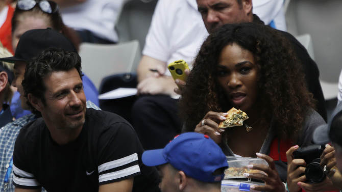Serena Williams, right, of the US watches her sister Venus during her first round match against Kazakstan's Galina Voskoboeva at the Australian Open tennis championship in Melbourne, Australia, Monday, Jan. 14, 2013. (AP Photo/Rob Griffith)