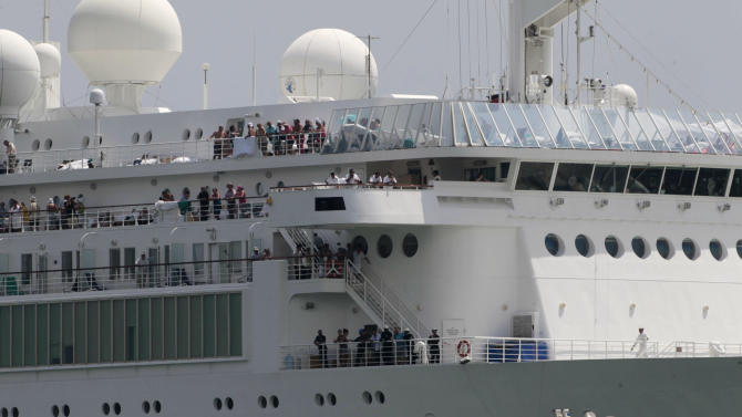 Passengers look out from the Costa Allegra cruise ship as it is towed in the Victoria's harbor, Seychelles Island, Thursday, March 1, 2012. The disabled cruise ship arrived in port in the island nation of the Seychelles on Thursday morning after three days at sea without power. (AP Photo/Gregorio Borgia)