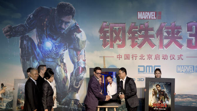 """U.S. actor Robert Downey Jr. center, shakes hands with Chinese actor Wang Xueqi after a photo session during a world premiere event of his new movie """"Iron Man 3"""" at a Beijing hotel Saturday, April 6, 2013. (AP Photo/Andy Wong)"""