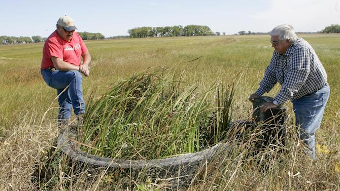 In this photo from Sept. 29, 2011, ranchers Todd Cone, left, and Terry Frisch stand by a cattle watering  circle where the Ogallala Aquifer water table is at ground level, in the sandhills near Atkinson, Neb., Thursday, Sept. 29, 2011. Cone said he still considers the Keystone XL pipeline a threat to the state's groundwater, but is too busy to keep fighting the project after it was rerouted away from near his property. Terry Frisch remains ardently opposed to the pipeline, even though the planned route has moved from near his property to about 10 miles away.(AP Photo/Nati Harnik)