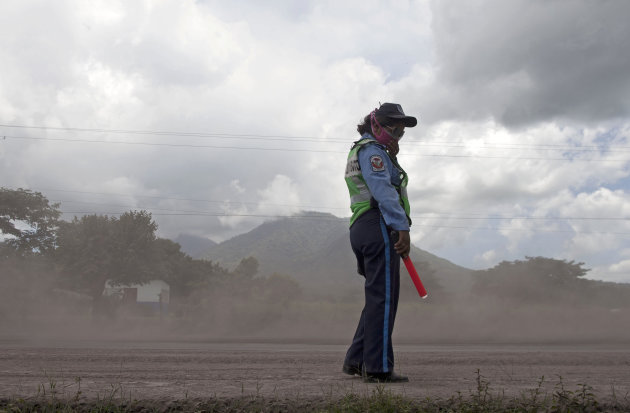 A Nicaraguan National Police officer patrols on a road blanketed with volcanic ash spewed from the San Cristobal volcano, near Chinandega, Nicaragua, Saturday, Sept. 8, 2012. Nicaragua's tallest volcano, located about 70 miles (110 kilometers) northwest of Managua, near the Honduran border, has let off a series of explosions, spewing gases and showering ash on nearby towns, prompting an evacuations of residents. (AP Photo/Esteban Felix)