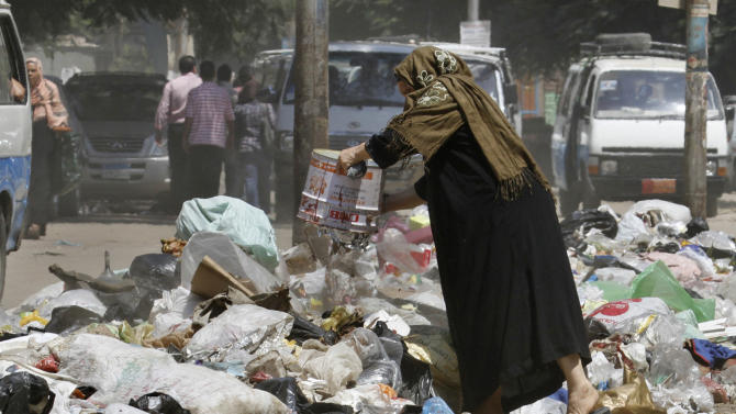 In this Thursday, Aug. 16, 2012 photo, a woman throws her waste in a street in Cairo. A government modernization effort flopped. A swine flu panic prompted the mass slaughter of the pigs that recycled Cairo's organic garbage; the city's metal trash bins were easy prey for thieves, especially during the global scrap metal boom. Now the garbage crisis in the Arab world's biggest city is posing a significant test for the newly elected government that replaced longtime autocratic leaders. (AP Photo)