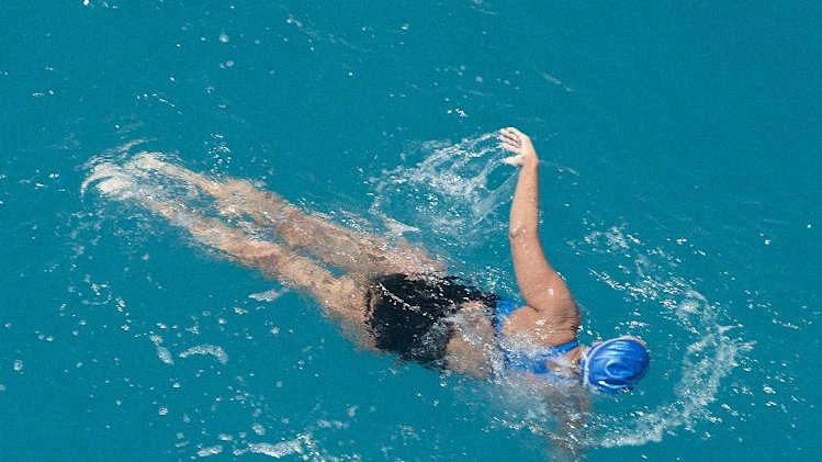 In this photo provided by the Florida Keys News Bureau, Diana Nyad, positioned about two miles off Key West, Fla., Monday, Sept. 2, 2013, swims towards the completion of her approximately 110-mile trek from Cuba to the Florida Keys. Nyad, 64, on Monday became the first person to swim from Cuba to Florida without the help of a shark cage. (AP Photo/Florida Keys News Bureau, Andy Newman)
