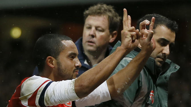 Arsenal's Theo Walcott gestures to the crowd to show the score of 2-0, as he is stretchered off in front of Tottenham fans during the English FA Cup third round soccer match between Arsenal and Tottenham Hotspur at the Emirates Stadium in London, Saturday, Jan. 4, 2014. Arsenal won the match 2-0. (AP Photo/Kirsty Wigglesworth)