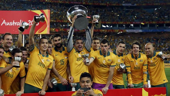 Australia's Massimo Luongo takes a selfie with his teammates celebrating behind him with their trophies and the Asian Cup after they beat South Korea to win the tournament at the Stadium Australia in Sydney