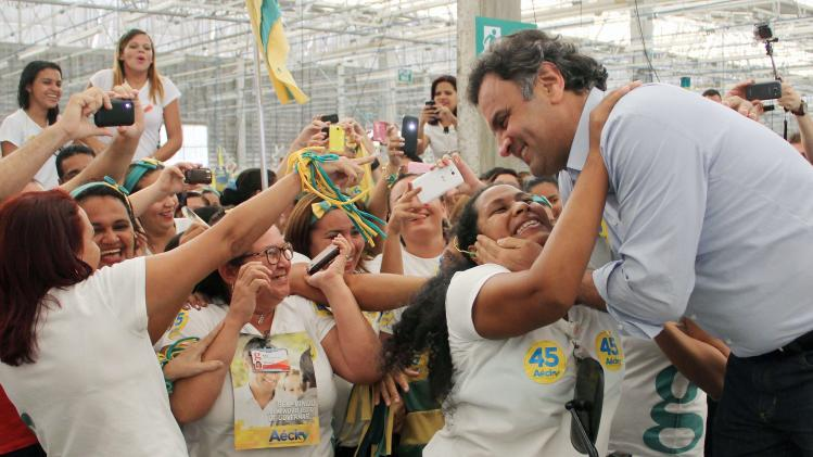 Presidential candidate Neves visits a clothing factory during his election campaign in Natal