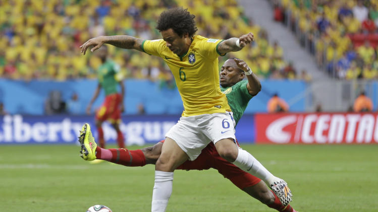 Brazil's Marcelo, left, is challenged by Cameroon's Eyong Enoh during the group A World Cup soccer match between Cameroon and Brazil at the Estadio Nacional in Brasilia, Brazil, Monday, June 23, 2014