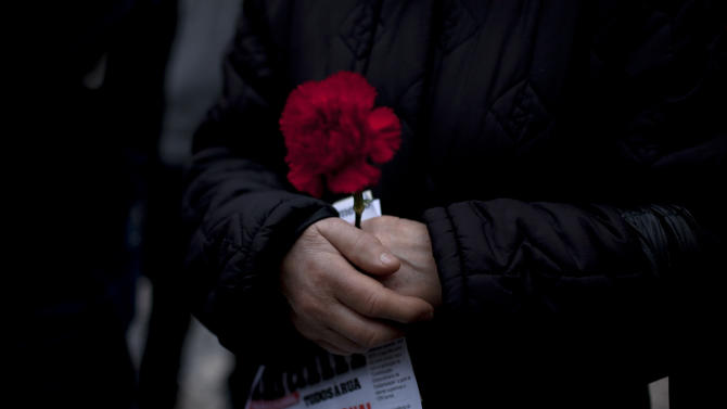 "A woman holds a red carnation and a leaflet with the words ""national shame"" during an anti-austerity protest march in Lisbon Saturday, Feb. 16 2013. The red carnation is the symbol of the April 25 1974 revolution that restored democracy in Portugal. The protest was called by CGTP, the Portuguese confederation of workers unions. (AP Photo/Armando Franca)"