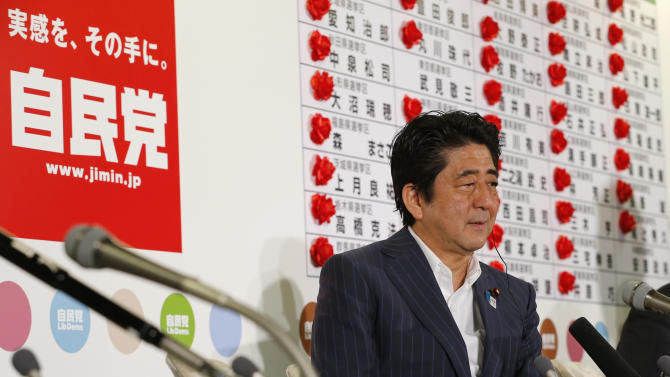"""Japanese Prime Minister Shinzo Abe listens to a reporter's question in front of red rosettes on the names of his Liberal Democratic Party's winning candidates during ballot counting for the upper house elections at the party headquarters in Tokyo Sunday, July 21, 2013. Abe's ruling coalition won a majority in the upper house of Parliament in elections, media projected, giving it control of both chambers and a mandate to press ahead with difficult economic reforms. A sign at left reads: """"Liberal Democratic Party."""" (AP Photo/Shizuo Kambayashi)"""