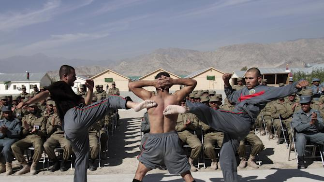 Newly graduated Afghan police officers demonstrate their skills during a graduation ceremony at a National Police training center in Laghman province, east of Kabul, Afghanistan, Wednesday, Nov. 7, 2012. Over 138 Local police officers graduated after receiving one months of training in Laghman. (AP Photo/Rahmat Gul)