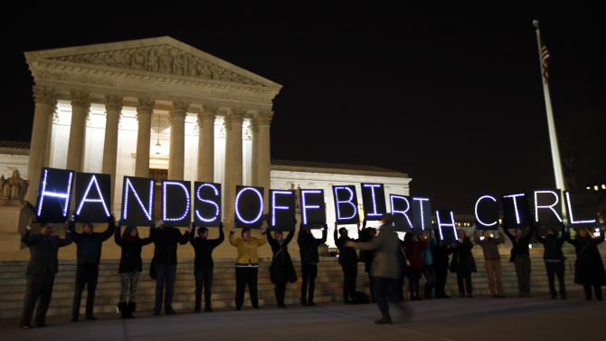 """A group of people organized by the NYC Light Brigade and the women's rights group UltraViolet, use letters in lights to spell out their opinion, in front of the Supreme Court, Monday, March 24, 2014, in Washington. Holding the """"H"""" in """"Hands"""" is Rep. Keith Ellison, D-Minn. The Supreme Court is weighing whether corporations have religious rights that exempt them from part of the new health care law that requires coverage of birth control for employees at no extra charge. (AP Photo/Alex Brandon)"""