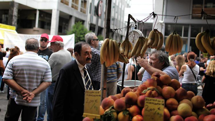 A street vegetable vendor discusses Greece's crisis with a man  as in the background is seen a protest outside the ministry of Finance, in central Athens, on Wednesday, Sept. 12, 2012. A fresh wave of anti-austerity strikes hit Greece Wednesday as the leaders of the governing coalition struggled to finalize further spending cuts for the coming two years — without which the country will lose its vital rescue loans.(AP Photo/Petros Giannakouris)