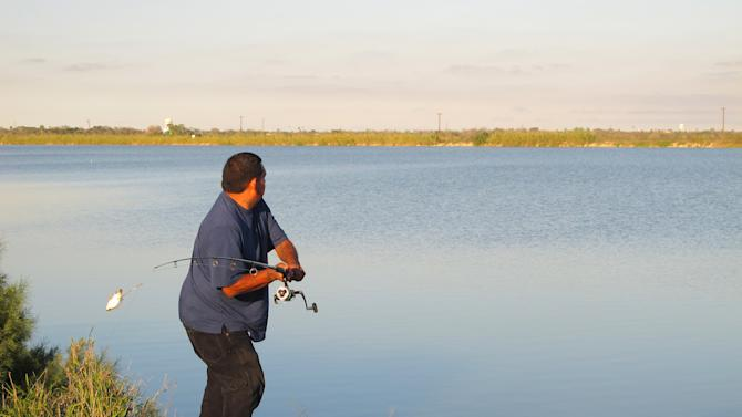 In this Feb. 13, 2012 photo, Joe Garcia fishes along Donna Reservoir in Donna, Texas. The lake's fish have long been known to carry harmful chemicals, but fishermen keep coming back in spite of warning signs. (AP Photo/Chris Sherman)