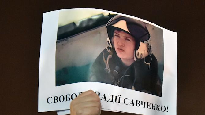"""A demonstrator holds a picture of Ukranian army officer captured by pro-Russian insurgents, Nadiya Savchenko, bearing the slogan """"Free Nadiya Savchenko"""" during a rally for her release on Independence Square in Kiev, Ukraine, on January 26, 2015"""