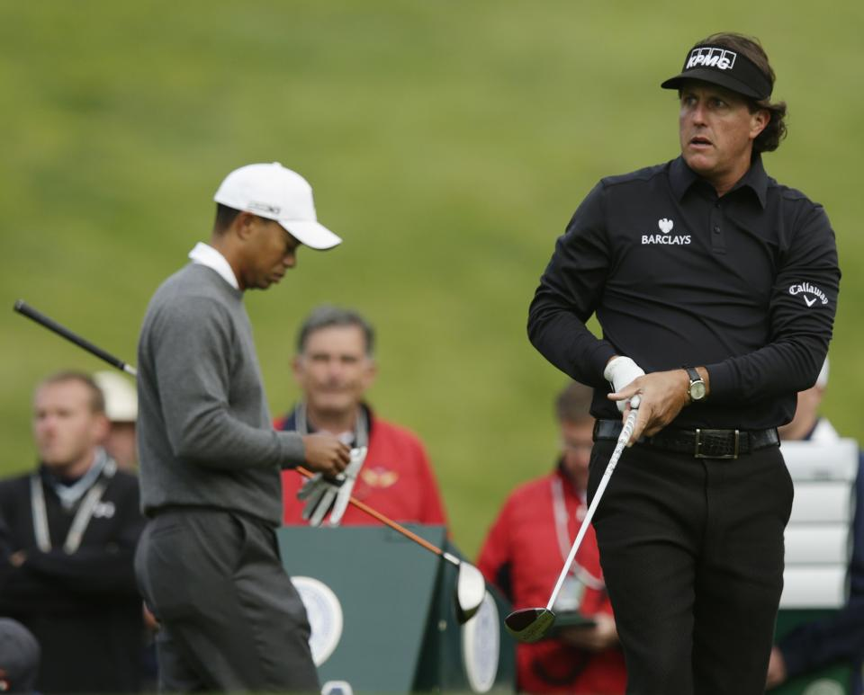 Phil Mickelson watches his drive on the ninth hole as Tiger Woods gets ready to tee off during the first round of the U.S. Open Championship golf tournament Thursday, June 14, 2012, at The Olympic Club in San Francisco. (AP Photo/Charlie Riedel)