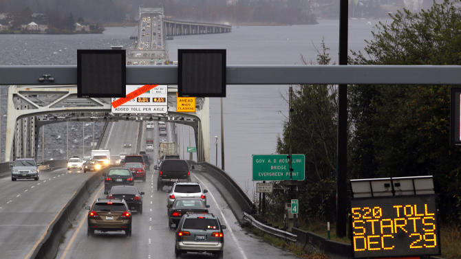 FILE - In this Dec. 28, 2011 file photo, traffic moves across the Highway 520 floating bridge toward Seattle from Medina, Wash., as a sign announces the start of tolling. Republican gubernatorial candidate Rob McKenna says Washington state's multi-billion dollar transportation needs could ultimately require voter-approved taxes, but his Democratic counterpart, Jay Inslee, isn't yet ready to support any specific financing plan. (AP Photo/Elaine Thompson, file)