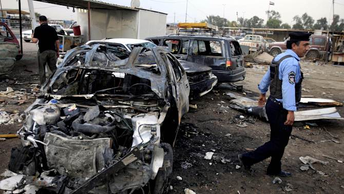 A policeman inspects the aftermath of a car bomb attack at a used cars dealers parking lot in Habibiya neighborhood of eastern Baghdad, Iraq, Tuesday, April 16, 2013. Less than a week before Iraqis in much of the country are scheduled to vote in the country's first elections since the 2011 U.S. troop withdrawal, a series of attacks across Iraq on Monday, many involving car bombs, has killed and wounded dozens of people, police said. (AP Photo/Karim Kadim)
