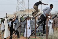 <p>Sudanese protesters climb over a fence outside the US embassy in Khartoum on September 14 during a protest against an amateur film mocking Islam. Furious protesters targeted symbols of US influence in cities across the Muslim world on Friday, attacking embassies, schools and restaurants in retaliation for a film that mocks Islam.</p>