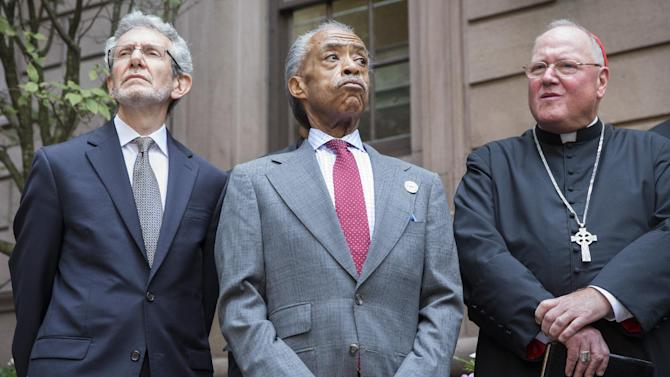 Rev. Al Sharpton, center, attends a press conference alongside Rabbi Michael Miller, left, Executive VP and CEO of the Jewish Community Relations Council of NY, and Cardinal Timothy Dolan, right, following a multi-faith roundtable meeting Wednesday, Aug. 20, 2014, in New York, spawned by the death of Eric Garner, a Staten Island man who was placed in an apparent chokehold by a police officer, The mayor says he believes the meeting can help a city gripped by protests and distrust of the police in some minority neighborhoods. (AP Photo/John Minchillo)
