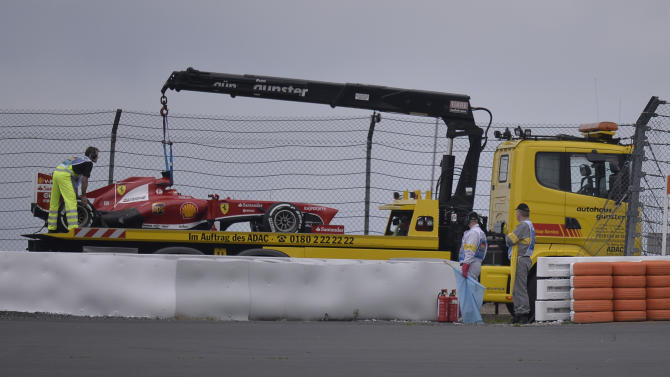 Ferrari driver Fernando Alonso car is carried out of the track by marshals after failing to complete the first free paractice at the Nuerburgring racetrack, in Nuerburg, Germany, Friday, July 5, 2013. The Formula one race will be held on Sunday. (AP Photo/Martin Meissner)