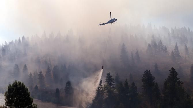 A helicopter drops water taken from the adjacent Yakima River onto a wildfire Tuesday, Aug. 14, 2012, on Highway 10 near Cle Elum, Wash. The fast-moving wildfire has burned 60 homes across nearly 40 square miles of central Washington grassland, timber and sagebrush. No injuries have been reported but more than 400 people have been forced to flee. (AP Photo/Elaine Thompson)