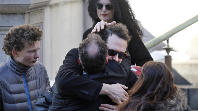Writer David Bar Katz is embraced as he arrives at the Church of St. Ignatius Loyola for the private funeral of actor Philip Seymour Hoffman Friday, Feb. 7, 2014, in New York. Hoffman, 46, was found dead Sunday of an apparent heroin overdose. (AP Photo/Jason DeCrow)