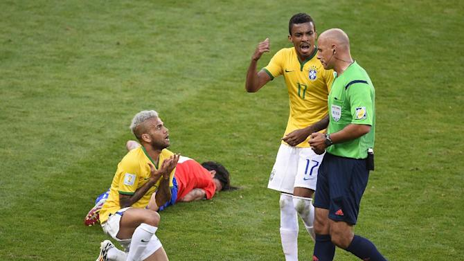 Brazil's defender Dani Alves (L) and Brazil's midfielder Luiz Gustavo (C) speak with British referee Howard Melton Webb during extra-time of the match between Brazil and Chile at the Mineirao Stadium in Belo Horizonte on June 28, 2014