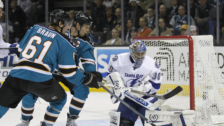Tampa Bay Lightning goalie Dwayne Roloson (30) blocks a shot attempt by San Jose Sharks center Joe Thornton (19) and San Jose Sharks defenseman Justin Braun (61) during the second period of an NHL hockey game in San Jose, Calif., Wednesday, Dec. 21, 2011. (AP Photo/Tony Avelar)