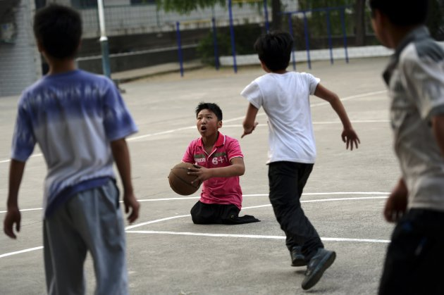 Basketball fan Qin prepares to make a shot at a middle school in Yichuan county, Luoyang