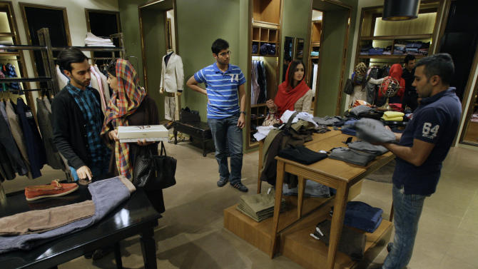 In this photo taken on Wednesday, Oct. 24, 2012, potential Iranian customers talk as a shopkeeper, right, adjusts the merchandise in a clothing store, in Tehran, Iran. Iranian authorities have been forced to quell protests in recent weeks over the plummeting value of the country's currency which lost nearly 40 percent of its value against the U.S. dollar in a week in early October. With the U.S. election less than 10 days away, both President Obama and Republican challenger Mitt Romney are cautious about discussing potential compromises as Iran's economy shows signs of increasing strain from economic sanctions that seek nuclear concessions. (AP Photo/Vahid Salemi)