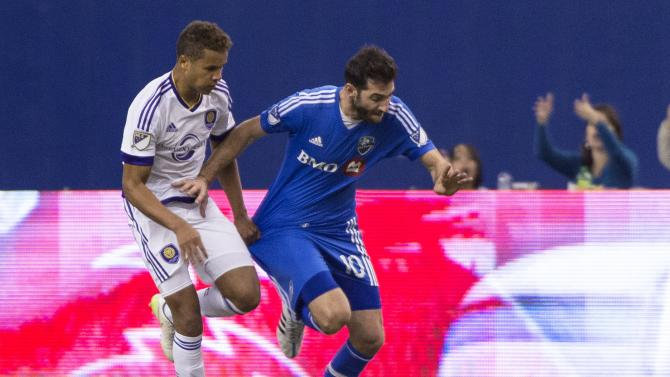 Orlando City SC's Tyler Turner, left, tugs on Montreal Impact's Ignacio Piatti's jersey during second-half MLS soccer game action on Saturday, March 28, 2015, in Montreal. (AP Photo/The Canadian Press, Paul Chiasson)