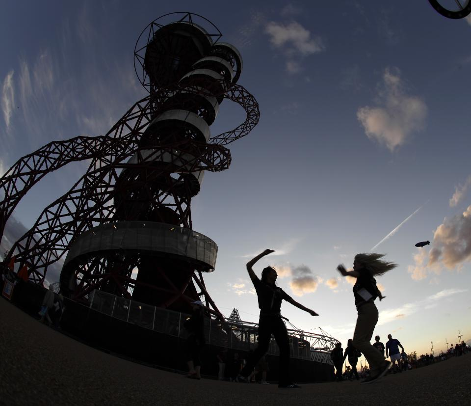 In this Friday, Aug. 3, 2012 photo, two women dance to music on loudspeakers under the Orbit attraction at Olympic Park during the 2012 Summer Olympics, in London. (AP Photo/Charlie Riedel)