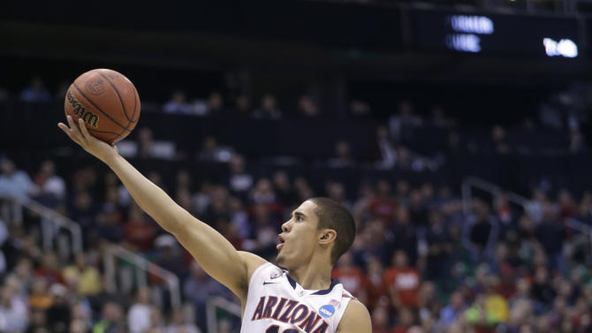 Arizona's Nick Johnson (13) lays the ball up next to Harvard's Christian Webster in the first half during a third-round game in the NCAA men's college basketball tournament in Salt Lake City, Saturday, March 23, 2013. (AP Photo/Rick Bowmer)