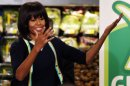 "First lady Michelle Obama gestures to the crowd at a Walmart Neighborhood Market in Springfield, Mo., Thursday, Feb. 28, 2013. Obama was promoting her campaign against childhood obesity and highlight ""the groundbreaking steps"" the retailer has taken to make healthy food more affordable.(AP Photo/Orlin Wagner)"
