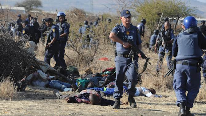 Police surround the bodies of striking miners after opening fire on a crowd  at the Lonmin Platinum Mine near Rustenburg, South Africa, Thursday, Aug. 16, 2012. An unknown number of people have been killed and injured when police moved in on workers who gathered on a rocky outcrop  near the Lonmin late afternoon, firing unknown ammunition.  (AP Photo)