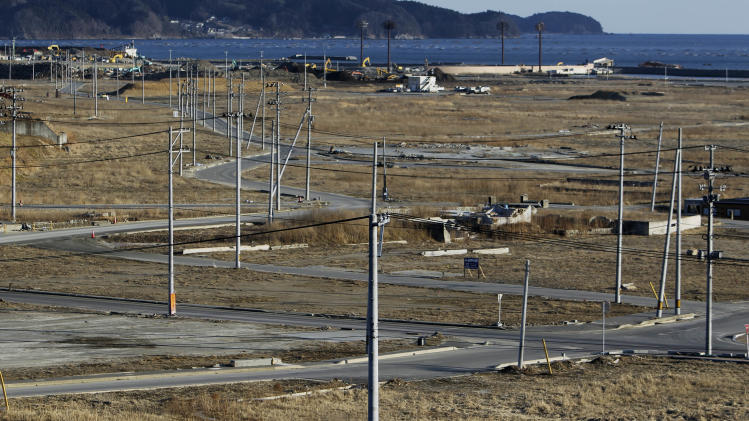 In this Friday, Feb. 22, 2013 photo, utility poles are erected in an area devastated by the March 11, 2011 earthquake and tsunami, in Rikuzentakata, Japan. About three-quarters of Rikuzentakata's 8,000-some homes were destroyed by the 13-meter (43-foot) tsunami that swept up to 4 kilometers (two and a half miles) up its wedge-shaped river valley. Most debris was hauled away long ago. The wind whips through derelict skeletons of the few concrete buildings yet to be demolished. Utility poles stud roadsides and empty lots littered with mundane odds and ends - kitchen strainers, skillets, laundry hangers, a rusted clock.(AP Photo/Junji Kurokawa)