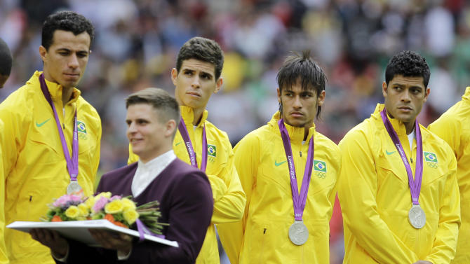 Brazil players react on the podium as they receive the silver medal during a ceremony following their loss to Mexico in the men's soccer final at the 2012 Summer Olympics, Saturday, Aug. 11, 2012, in London. (AP Photo/Hussein Malla)