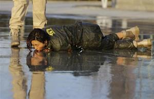 A female trainee lies on the ground after being drenched with water during Tianjiao Special Guard/Security Consultant training on the outskirts of Beijing December 1, 2013. REUTERS/Jason Lee