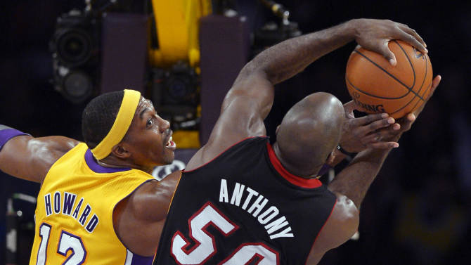 Los Angeles Lakers center Dwight Howard (12) reaches for a rebound with Miami Heat center Joel Anthony during the first half of their NBA basketball game, Thursday, Jan. 17, 2013, in Los Angeles. (AP Photo/Mark J. Terrill)