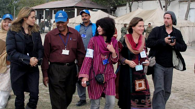 FILE - In this Saturday, Nov. 26, 2005, file photo, Hollywood actress and United Nations High Commissioner for Refugees Ambassador Angelina Jolie, left, and actor Brad Pitt, right, are escorted by unidentified UNHCR officials towards a helicopter in Muzaffarabad, Pakistan, after seeing an earthquake-affected area. Jolie and Pitt were married Saturday, Aug. 23, 2014, in France, according to a spokesman for the couple. (AP Photo/Roshan Mughal, File)