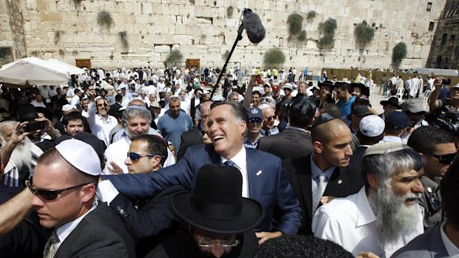 Republican presidential candidate and former Massachusetts Gov. Mitt Romney greets the crowd after he visited the Western Wall, rear, in Jerusalem, Sunday, July 29, 2012. (AP Photo/Charles Dharapak)