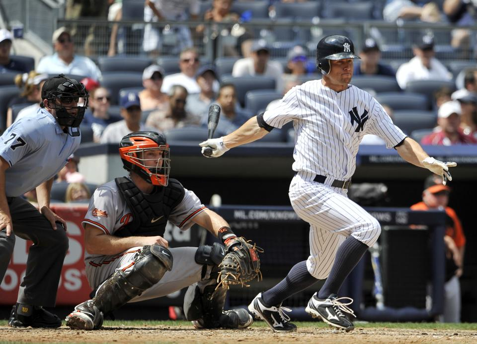 Home plate umpire Jim Reynolds, left, and Baltimore Orioles catcher Craig Tatum, center, watch New York Yankees' Brett Gardner, right, hit a three-run triple off starting pitcher Jake Arrieta in the fourth inning of a baseball game on Sunday, July 31, 2011, at Yankee Stadium in New York. (AP Photo/Kathy Kmonicek)