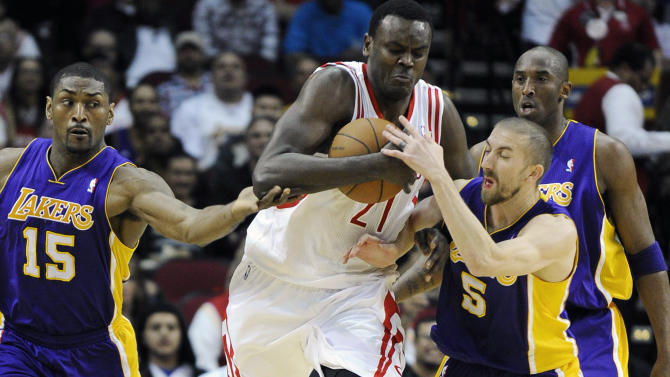 Houston Rockets' Samuel Dalembert (21) tries to break through the defense of Los Angeles Lakers Metta World Peace (15), Steve Blake (5) as Lakers' Kobe Bryant watches in the first half of an NBA basketball game Tuesday, March 20, 2012, in Houston. (AP Photo/Pat Sullivan)
