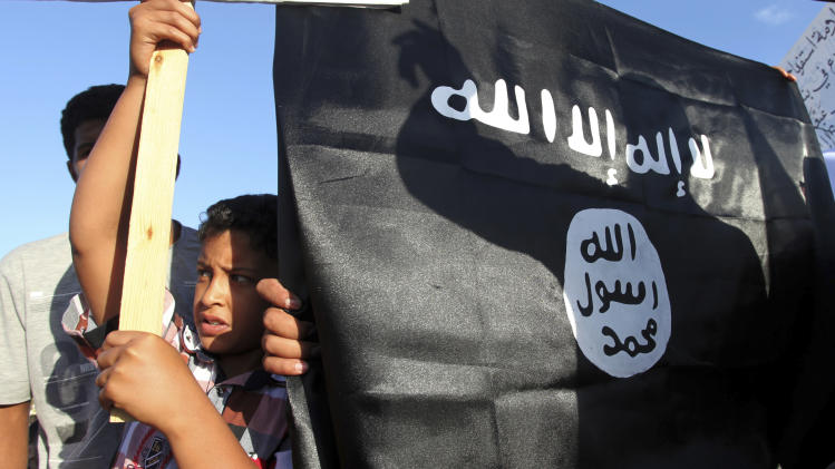A Libyan follower of Ansar al-Shariah Brigades' shadow reflects on the flag of the Brigades, while he gives a speech at the Victory Square, against a film and a French cartoon denigrating the Prophet Muhammad, in Benghazi, Libya, Friday, Sept. 21, 2012. The attack that killed the U.S. ambassador and three other Americans has sparked a backlash among frustrated Libyans against the heavily armed gunmen, including Islamic extremists, who run rampant in their cities. more than 10,000 people poured into a main boulevard of Benghazi, demanding that militias disband as the public tries to do what Libya's weak central government has been unable to.(AP Photo/Mohammad Hannon)