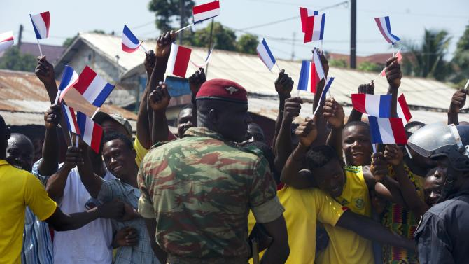 A soldier stands guard as people wave flags while they line the streets to greet French President Francois Hollande in Conakry