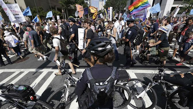 Police officers observe protestors marching, Sunday, Sept. 2, 2012, in Charlotte, N.C. Demonstrators are protesting before the start of the Democratic National Convention. (AP Photo/Patrick Semansky)