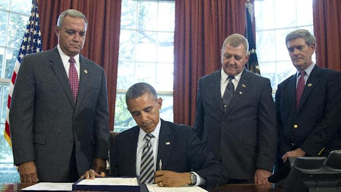 FILE - President Barack Obama signs the Honoring America's Veterans and Caring for Camp Lejeune Families Act of 2012 on Monday, Aug. 6, 2012, in the Oval Office at the White House in Washington. From left are, Rep. Jeff Miller, R-Fla., Jerry Ensminger, former Master Sergeant, USMC, who served at Camp Lejeune and advocated on behalf of affected veterans and families, and Rep. Brad Miller, D-N.C. Ensminger blames contaminated water at Camp Lejeune for the leukemia that killed his 9-year-old daughter. (AP Photo/Haraz N. Ghanbari)