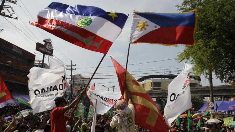 Filipino Muslim men wave flags of the Philippines, right, and Autonomous Region in Muslim Mindanao during a rally in support of a preliminary peace pact between the government and the nation's largest Muslim rebel group during a rally outside the gates of the Malacanang presidential palace in Manila, Philippines, on Monday Oct. 15, 2012. Muslim rebels and the Philippine government overcame decades of bitter hostilities and took their first tentative step toward ending one of Asia's longest-running insurgencies with the ceremonial signing of a preliminary peace pact Monday that both sides said presented both a hope and a challenge. (AP Photo/Aaron Favila)